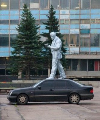 Statue is standing above the car illusion
