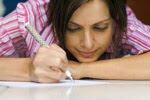 Девушка пишет на листе бумаги