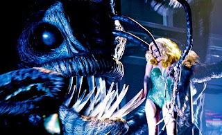 Lady Gaga cowers before the giant angler fish, which is about to eat her alive