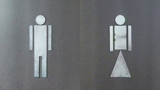 Two rectangular stick figures, one with legs, another with a  triangle where the legs should be