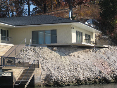 a home built on the edge of the shoreline. The ground underneath the foundation is severely eroded