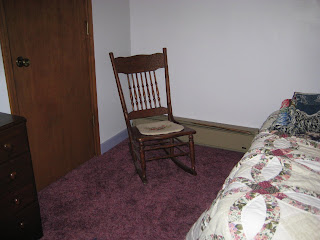 an old spindle rocking chair with a needle point seat