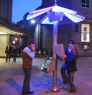 Picture shows the PDWeb Umbrella in Aberdeen Scotland with two people using one of the twin touch screens; another person is using his mobile phone (Skype) via a free webLink WiFi MESH connection to make calls. The Umbrella is a visible part of the FREE public access service: many more unseen users connect  over the Umbrella Hubs WiFi option!