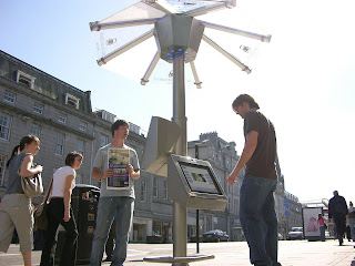 Daytime photograph of user and passers by at one of the PDWeb Umbrella's: These architecturally designed street furniture units provide the citizens and visitors to the city with FREE digital public access to the internet via these hubs on Union Street in Aberdeen Scotland.