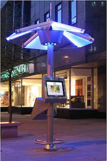 From concept to street deployment the PUBLIC DATAWEB UMBRELLA kiosk operating in the city centre in Aberdeen Scotland. The picture shows the kiosk at night with its illuminated top Umbrella highlighting the area in a pool of blue light. © PUBLIC DATAWEB