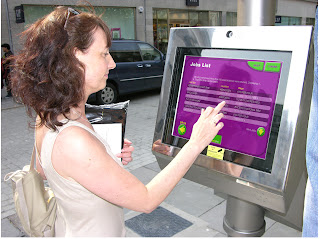 Picture shows a person using the touch screen: seeking local job vacancies. The screen is housed in a robust all weather frame. The touch screen is held beneath a special reinforced laminated glass membrane which is vandal hardened and easy to replace id seriously attacked. These things happen but the touch screen is safe beneath its protective replaceable barrier. Operating in Aberdeen since 2006. © PUBLIC DATAWEB