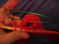 Mitt with thumb gusset completed, placing thumb stitches on a holder and continuing palm.