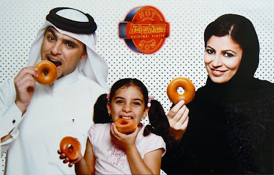 A family in Qatar National Dress munch on Krispey Kreme donuts in a Kripsey Kreme advertisement