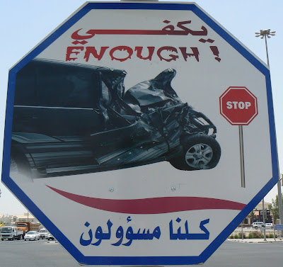 Enough, reads a sign in Doha, Qatar, next to a picture of a destroyed car