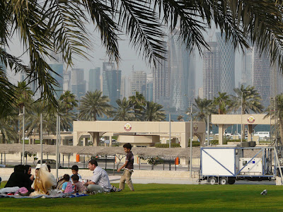 A family picnic in a Doha park, with the city's skyline in the background