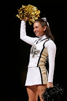 White uniformed brunette University of Central Florida cheerleader holds up a golden pom pom against a black night sky.