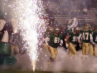 football players in green and yellow uniforms take the field amongst fireworks and smoke.