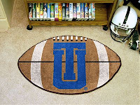 Carpeted den with blue UT written over a brown football in the carpet.  Football helmet and VHS tapes in the background.