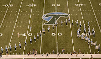Marching band takes a football field and forms a wave formation at the fifty yard line around a T with a wave drawn over it at midfield.