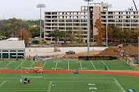 Aerial view of a college football practice facility with a track around the field and construction of tall building in the background.