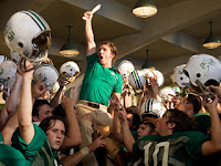 Actor Matthew McConaughey portraying a Marshall University football coach being hoisted up by players from the football team in a locker room scene in the movie We Are Marshall.