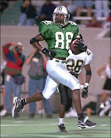 Randy Moss wearing a green Marshall uniform runs into the end zone to score a touchdown in a college football game.