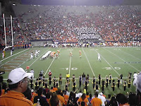 Fans in orange t-shirts look upon a night football game where a goal line stand occurs between a team in orange uniforms against a team in white uniforms.
