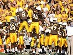 Wyoming football players celebrate a big play during a game.