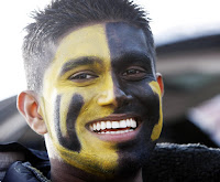 University of Idaho fan with face painted yellow and black.