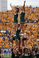CSU cheerleaders in green uniforms at football game.