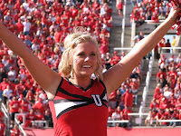 Utah cheerleader in red uniform at football game.