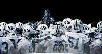 BYU football team huddles at night in white uniforms.