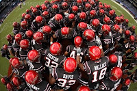 Overhead view of SDSU football team in black uniforms huddle before a game.