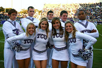 Texas Christian cheerleaders pose in white uniforms.