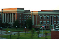 Three story brick building with white columns at dusk on the University of Memphis campus.