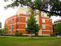 Four story red brick academic building on a green lawn on the Marshall University campus.