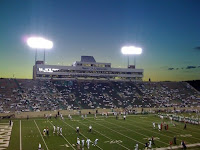 A Marshall University football game played under stadium lights as the sun sets.