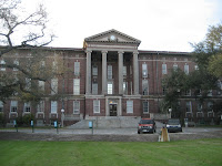 Three story wide rectangular building with four distinct columns.  Stairs leading up to the majestic dated brick structure merge from green lawn in front of the building.
