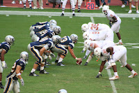 Rice University football lines up to snap the ball at the line of scrimmage.