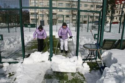 Quitando nieve de la pista de padel