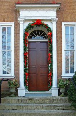 the mansion's beautiful wood doors were decorated with garland for the Christmas season