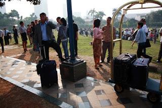 WNA keluar dari hotel dan apartemen dengan membawa koper besar dengan berjalan kaki menuju luar gedung.