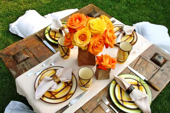 Outdoor picnic table with plaid enamel plates and cups, a simple white runner and an original centerpiece made of gorgeous orange roses in brown paper bags by Lily Lodge