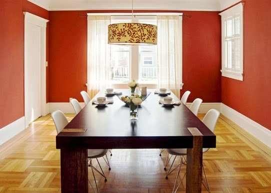Red dining room with long modern wood table, hand painted drum chandelier and plastic Eames chairs by Niche Interiors