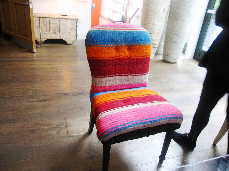 Chair with a curved back and spindle legs upholstered in a Mexican blanket like fabric in the Crosby Street Hotel
