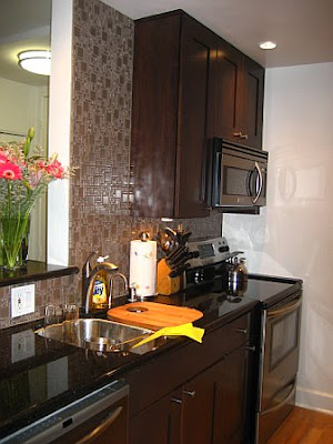 Kitchen after remodeling with black counter tops, dark wood cabinets and tile backsplash up to the ceiling