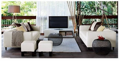 Outdoor patio with white dueling sofas, two white square ottomans, a TV and two round link side tables from cb2