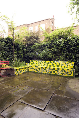 London garden with a green and yellow mosaic bench and fountain