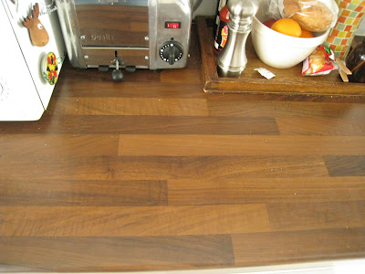 Dark brown wood butcher block counters in a small London kitchen