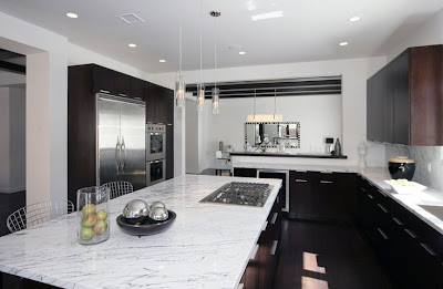 Black and white kitchen with a huge island with marble counter top, dark wood cabinets and drawers and stainless appliances