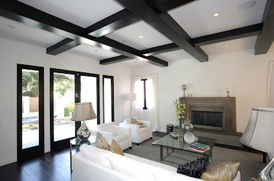 Black and white living room with painted black exposed beams, a white sofa  and two large comfy white armchairs