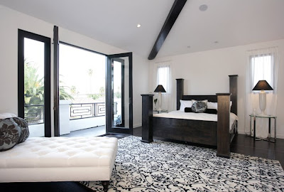 Black and white master bedroom with double French doors opening to a balcony, a Moroccan print rug and a large black four poster bed