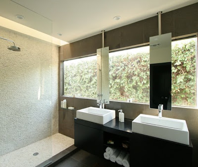 Modern bathroom after The Sunset Team/La Kaza Design's remodeling with large picture window, dark vanity and a shower tiled with pebble mosaic tiles
