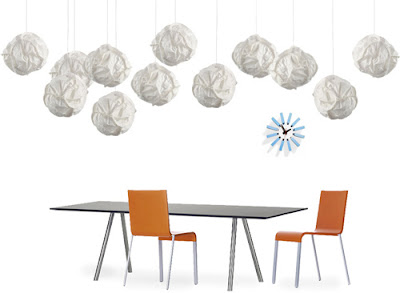 Cloud pendant lights design by Frank Gehry over a long modern table