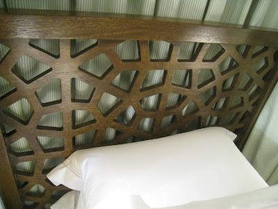 Custom dark wood modern lattice headboard in a guest bedroom in the Greystone Mansion